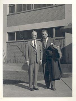 Portrait of E.V. Cowdry and an unidentified man standing in front of a building.