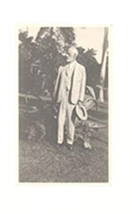 Nathaniel Harrington Cowdry standing in a garden, holding a hat in his hand.