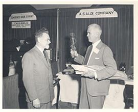 E.V. Cowdry holding a small metal statue and conversing with an unidentified man in a vendor boot...
