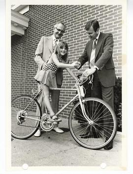 Herb Kaufmann and Jack Hughes presenting Shannon Cook with a 10-speed bicycle.