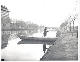 Man standing in a wooden boat on a river or canal, China.