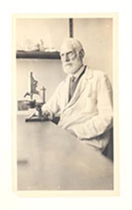 Portrait of Nathaniel Harrington Cowdry sitting in front of a microscope in a laboratory.