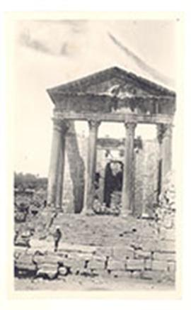 E.V. Cowdry, Jr. posed on the steps of stone temple ruins, Dougga, Tunesia.