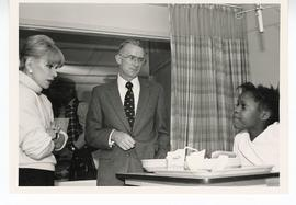 Joan Rivers and Ron Evens speaking with a patient in bed, St. Louis Children's Hospital.