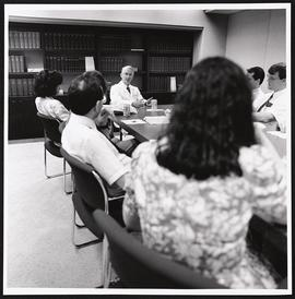 Ronald G. Evens seated at the head of a board room table.