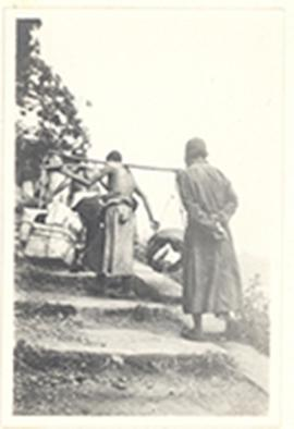 Two men ascending steps, one of whom is carrying balanced bundles on a pole across his shoulders,...