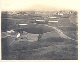 View of Chinese farmland with roads, a mountain, and a distant institutional building.