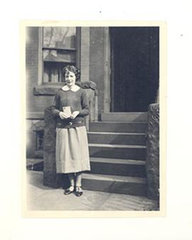 Portrait of Alice Cowdry holding a letter at the foot of the front steps of a brownstone.