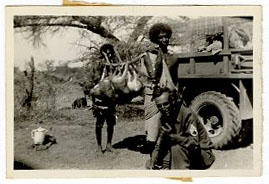 Soldier posing with two Eritreans carrying a gazelle.