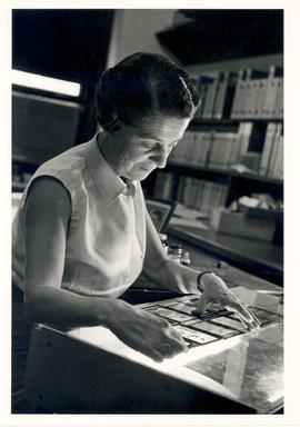 Rita Levi-Montalcini examining negatives in her office.