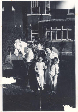 Patients and nurses posing next to a horse, St. Louis Children's Hospital.