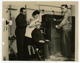 Three men and a woman demonstrating Electroencephalography.