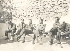 Seated officers on an upper porch at the Hotel Obadia, Bou Hanifia, Algeria.