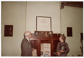 Unidentified man and Judith Baumgarten examining a framed commemoration at a St. Louis Medical So...