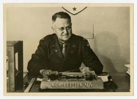 Col. Lee D. Cady sitting at a desk.