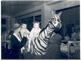 "Patients riding a ""zebra"" with clowns assisting them, St. Louis Children's Hospital."