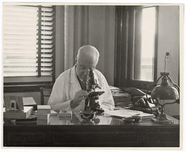 Evarts A. Graham looking through a microscope.