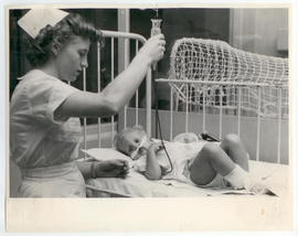 Nurse holding an IV/feeding tube over a patient.