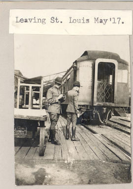 Two soldiers on a train platform.