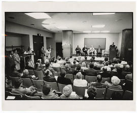 View of the audience, news crews, and stage as Robert E. Frank gives a speech at the West Pavilio...