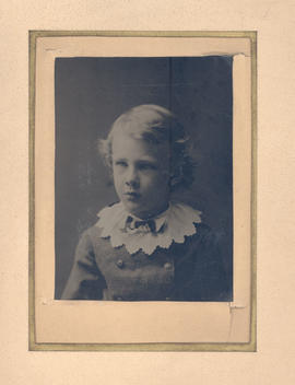 Portrait of blond child, around eight years old, wearing buttoned jacket and white collar.