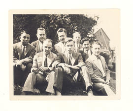 Group portrait of Hiromu Tsuchiya and seven unidentified friends seated on grass.