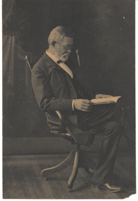 Dr. Gustav Baumgarten seated with book.