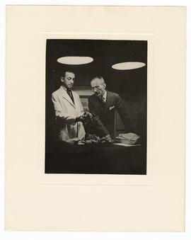 Two unidentified doctors examining a specimin.