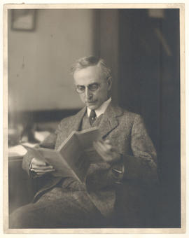 Leo Loeb seated and reading in his office.