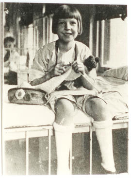 Female patient knitting on a bed, St. Louis Children's Hospital.