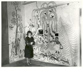 Gisella Loeffler posing with her artwork in the operating room of Vilray P. Blair.