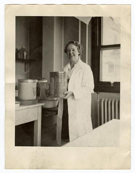 Margaret G. Smith in her lab, holding a popcorn tin.