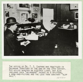 Dr. T.S. Chapman meeting with a patient in his office.