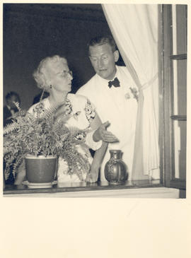 Helen Tredway Graham standing by a window with an unidentified man.