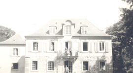 Exterior view of Chateau Charles with General Hospital 21 personnel posing in some windows and do...
