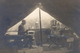 Edwin C. Ernst seated in his tent.