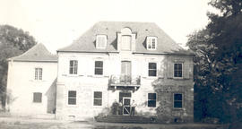Exterior view of Chateau Charles with General Hospital 21 personnel standing at the front door.