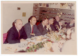 Robert J. Glaser and a group of unidentified men at a dinner party.