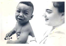 Nurse holding a crying infant, St. Louis Children's Hospital.
