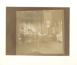 Dr. Gustav Baumgarten sitting in a rocking chair in his living room on Chestnut Street. St. Louis...