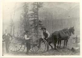 Group portrait of Vilray P. Blair and two unidentified men posing next to a cart pulled by two ho...