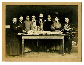Group portrait of James W. Wells and seven other men posing with their dissected cadaver in the B...