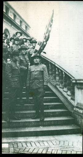 Uniformed American officers posed on a staircase holding an American flag.
