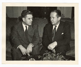 John R. Heller, Jr., and Leonard Andrew Scheele seated on a couch, conversing.