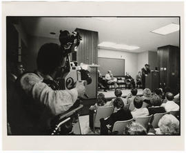 View of the audience and a news camera fiming Robert E. Frank addressing the audience at the West...