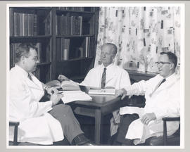 Carl F. Cori (center) and two unidentified doctors seated around a table.