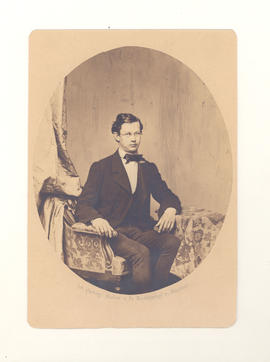 Gustav Baumgarten sitting for portrait in studio chair with draperies.